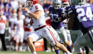 FILE - In this Oct. 17, 2015, file photo, Oklahoma quarterback Baker Mayfield carries the ball during his team's NCAA college football game against Kansas State in Manhattan, Kan. Mayfield has been awarded the Burlsworth Trophy, annually given to college football's most outstanding player who began his career as a walk-on. (AP Photo/Nati Harnik, File)
