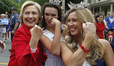 FOR USE AS DESIRED, YEAR END PHOTOS - FILE - Democratic presidential candidate Hillary Rodham Clinton flexes her muscles with Miss Teen New Hampshire Allie Knault, center, and Miss New Hampshire Holly Blanchard, during a Fourth of July parade, Saturday, July 4, 2015, in Gorham, N.H. (AP Photo/Robert F. Bukaty, File)