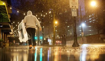 A person carries his dry cleaning while walking in the rain through midtown Atlanta on Wednesday. In parts of Georgia, including Atlanta, a flood watch was posted through Friday evening, the National Weather Service said. (Associated Press)