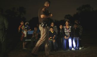A group of  immigrants from Honduras and El Salvador who crossed the U.S.-Mexico border illegally are stopped on June 25, 2014, in Granjeno, Texas. (Associated Press)