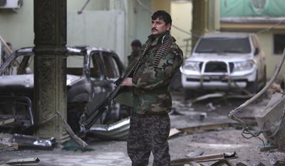 An Afghan security forces member stands guard at the Spanish Embassy after an attack in Kabul on Dec. 12. Explosions and gunfire rocked a diplomatic area of central Kabul overnight as security forces tried to flush out Taliban attackers who claimed responsibility for a deadly car bomb Friday. (Associated Press)