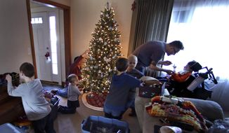 In this Saturday, Dec. 12, 2015 photo, Eric Volz-Benoit, a registered nurse who works with children afflicted with complex medical disabilities, attends to his adopted son, Zachary, right, who is wheelchair-bound after being born with cerebral palsy, while Eric's partner, Dennis, left rear, trims the Christmas tree at their family home in Springfield, Mass. Zachary is a patient participating in the Collaborative Consultative Care Coordinator Program, or 4C, where a team oversees all aspects of his care. (AP Photo/Charles Krupa)
