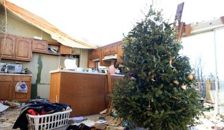 A Christmas Tree stands among damage done to a home on Falcon Road in Selmer, Tenn., Thursday, Dec. 24, 2015, after a tornado passed through the area Wednesday evening. No deaths or injuries were reported.  (Kenneth Cummings/The Jackson Sun via AP)