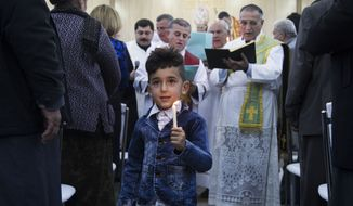 In this Thursday, Dec. 24, 2015 photo, a boy dressed in a tiny denim suit jacket holds a candle as Iraqi Christians celebrate during Christmas Eve mass in the Al-Bashara Church in a Christian refugee camp in Irbil, northern Iraq. Many of the worshippers are displaced from their homes after Islamic State militants swept through northern Iraq in 2014. (AP Photo/Seivan M.Salim)