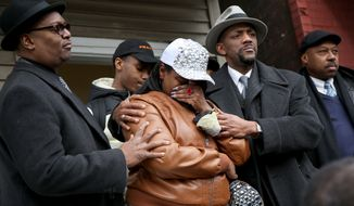 LaTarsha Jones, center, the daughter of Bettie Jones, is comforted by family and friends during a news conference on Sunday, Dec. 27, 2015, in front of the house where Bettie Jones was killed Saturday in the West Garfield Park neighborhood of Chicago. Grieving relatives and friends of two people shot and killed by Chicago police said Sunday that the city's law enforcement officers had failed its residents. (Nancy Stone/Chicago Tribune via AP) MANDATORY CREDIT