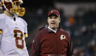 Washington Redskins head coach Jay Gruden, right, watches quarterback Kirk Cousins warm up before an NFL football game against the Philadelphia Eagles, Saturday, Dec. 26, 2015, in Philadelphia.  (AP Photo/Matt Rourke)