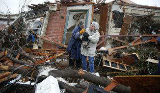Pam Russell, left, and Linda Hart rescue Pam's cat, Larue, from Russell's house a day after a tornado hit on Delta Drive in Rowlett, Texas, Sunday, Dec. 27, 2015. At least 11 people died and dozens were injured in apparently strong tornadoes that swept through the Dallas area and caused substantial damage this weekend. (Nathan Hunsinger/The Dallas Morning News via AP)
