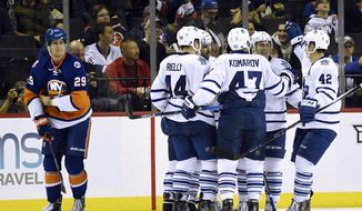 Toronto Maple Leafs defenseman Morgan Rielly (44), center Leo Komarov (47) and  center Tyler Bozak (42) celebrate right wing Michael Grabner's goal with teammates as New York Islanders center Brock Nelson (29) reacts during the second period of an NHL hockey game on Sunday, Dec. 27, 2015, in New York. (AP Photo/Kathy Kmonicek)
