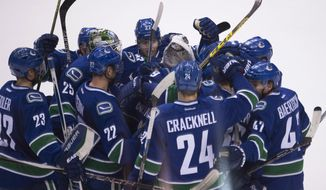 The Vancouver Canucks celebrate Jannik Hansen's goal in overtime against the Edmonton Oilers during an NHL hockey game Saturday, Dec. 26, 2015, in Vancouver, British Columbia. (Jonathan Hayward/The Canadian Press via AP)
