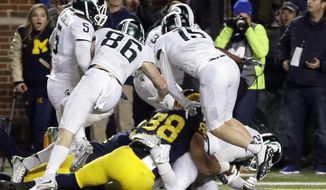 FILE - In this Oct. 17, 2015, file photo, Michigan State defensive back Jalen Watts-Jackson, lower right, falls into the end zone after recovering a fumbled snap on a punt in the closing seconds of the second half of an NCAA college football game in Ann Arbor, Mich. Michigan punter Blake O'Neill fumbled the snap and Watts-Jackson pulled it in, cradled it to his body and ran 38 yards for a touchdown. (AP Photo/Carlos Osorio, File)