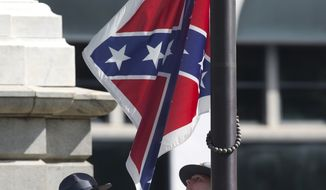 FILE - In a Friday, July 10, 2015 file photo, an honor guard from the South Carolina Highway patrol removes the Confederate battle flag from the Capitol grounds in Columbia, S.C., ending its 54-year presence there. (AP Photo/John Bazemore, File)