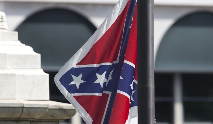 An honor guard from the South Carolina Highway patrol removes the Confederate battle flag from the Capitol grounds in Columbia, S.C., on July 10, 2015, ending its 54-year presence there. (Associated Press) **FILE**