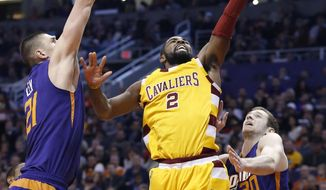 Cleveland Cavaliers' Kyrie Irving (2) drives past Phoenix Suns' Jon Leuer (30) and Alex Len (21), of Ukraine, to score during the first half of an NBA basketball game Monday, Dec. 28, 2015, in Phoenix. (AP Photo/Ross D. Franklin)