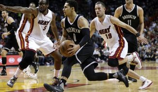 Brooklyn Nets' Shane Larkin (0) drives to the basket as Miami Heat's Amar'e Stoudemire (5) and Beno Udrih (19) defend during the half of an NBA basketball game, Monday, Dec. 28, 2015, in Miami. (AP Photo/Lynne Sladky)