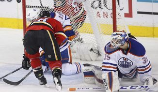 Edmonton Oilers goalie Anders Nilsson, right, from Sweden, watches as Calgary Flames' Matt Stajan bounces a puck into the goal during the second period of an NHL hockey game Sunday, Dec. 27, 2015, in Calgary, Alberta. (Larry MacDougal/The Canadian Press via AP)