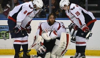 Washington Capitals left winger Alex Ovechkin (8), of Russia, and center Nicklas Backstrom (19), of Sweden, check on goaltender Braden Holtby (70) after a collision during the third period of an NHL hockey game against the Buffalo Sabres, Monday Dec. 28, 2015 in Buffalo, N.Y. Washington won 2-0. (AP Photo/Gary Wiepert)