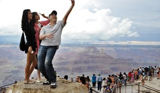 In this Aug. 2, 2015, photo, tourists Joseph Lin, Ning Chao, center, and Linda Wang, left, pose for a selfie along the south rim at Grand Canyon National Park, Ariz. The throngs of tourists have been showing up in big numbers at other national parks, including Yellowstone in Wyoming, Yosemite in California and Zion in Utah, driven by good weather, cheap gas and marketing campaigns ahead of next year's National Park Service centennial. (Emery Cowan/Arizona Daily Sun via AP/File) MANDATORY CREDIT