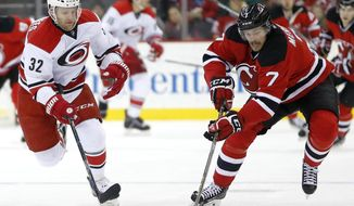 New Jersey Devils defenseman Jon Merrill (7) and Carolina Hurricanes right wing Kris Versteeg (32) compete for the puck during the first period of an NHL hockey game, Tuesday, Dec. 29, 2015, in Newark, N.J. (AP Photo/Julio Cortez)