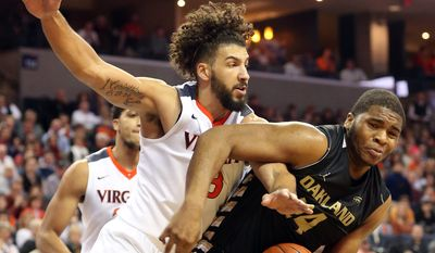 Virginia forward Anthony Gill (13) goes after the ball with Oakland center Percy Gibson, right, during an NCAA basketball game Wednesday, Dec. 30, 2015, in Charlottesville, Va. (AP Photo/Andrew Shurtleff)