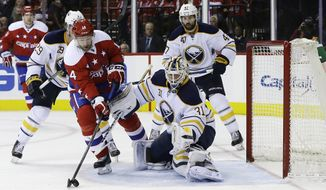 Buffalo Sabres goalie Chad Johnson (31) defends the goal as Washington Capitals right wing Justin Williams (14) controls the puck during the second period of an NHL hockey game, Wednesday, Dec. 30, 2015, in Washington. Moving in on the play are Sabres defensemen Jake McCabe (29) and Zach Bogosian (47). (AP Photo/Carolyn Kaster)