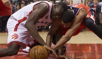 Toronto Raptors' Bismack Biyombo, left, battles for the ball with Washington Wizards' Garrett Temple during the first half of an NBA basketball game in Toronto, Wednesday, Dec. 30, 2015. (Chris Young/The Canadian Press via AP) MANDATORY CREDIT