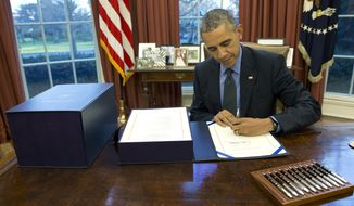 President Obama signs the budget bill in the Oval Office of the White House on Dec. 18, 2015, in Washington. (Associated Press)