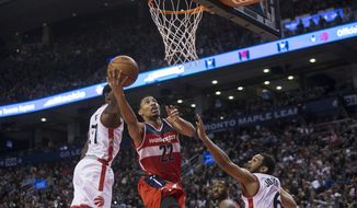 Washington Wizards' Otto Porter, center, scores on Toronto Raptors' Terrence Ross, left, and Corey Joseph during the second half of an NBA basketball game in Toronto on Wednesday, Dec. 30, 2015. (Chris Young/The Canadian Press via AP) MANDATORY CREDIT