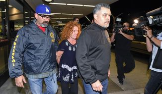 "Tonya Couch, center, is taken by authorities to a waiting car after arriving at Los Angeles International Airport, Thursday, Dec. 31, 2015, in Los Angeles. Authorities said she and her son, Texas teenager Ethan Couch, who was sentenced to probation after using an ""affluenza"" defense for a 2013 wreck in Texas, fled to Mexico together in November as prosecutors investigated whether he had violated his probation. Both were taken into custody Monday, Dec. 28, after authorities said a phone call for pizza led to their capture in the resort city of Puerto Vallarta. (AP Photo/Mark J. Terrill)"