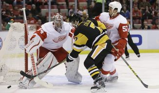 Detroit Red Wings goalie Petr Mrazek (34) deflects a shot by Pittsburgh Penguins center Matt Cullen (7) during the first period of an NHL hockey game, Thursday, Dec. 31, 2015, in Detroit. (AP Photo/Carlos Osorio)