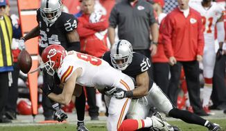 FILE - In this Dec. 6, 2015, file photo, Kansas City Chiefs tight end Travis Kelce, bottom right, loses a fumble as he is tackled by Oakland Raiders defensive back Nate Allen (20) during the first half of an NFL football game in Oakland, Calif. The Chiefs play the Oakland Raiders on Sunday, Jan. 3. (AP Photo/Marcio Jose Sanchez, File)