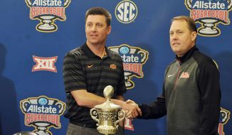 Oklahoma State head coach Mike Gundy, left, and Mississippi head coach Hugh Freeze pose with the trophy during a press conference for the Sugar Bow NCAA college football game, Thursday, Dec. 31, 2015, in New Orleans. (Bruce Newman/The Oxford Eagle via AP)
