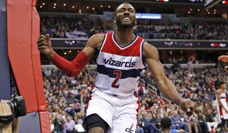 Washington Wizards guard John Wall (2) reacts after a basket in the second half of an NBA basketball game against the Orlando Magic, Friday, Jan. 1, 2016, in Washington. The Wizards won 103-91. (AP Photo/Alex Brandon)