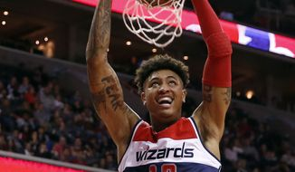 Washington Wizards forward Kelly Oubre Jr. (12) dunks the ball in the second half of an NBA basketball game against the Orlando Magic, Friday, Jan. 1, 2016, in Washington. The Wizards won 103-91. (AP Photo/Alex Brandon) **FILE**