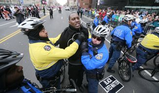 Police officers arrest protester Asa Khalif during the Mummers Day Parade on New Year's Day in Philadelphia on Friday, Jan. 1, 2016. Dozens of activists from the Black Lives Matter movement used the parade to stage a protest. (David Swanson/The Philadelphia Inquirer via AP) MANDATORY CREDIT