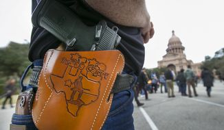 Terry Holcomb,executive director of Texas Carry, happily displays his customized holster as he walks to the Capitol for a rally, Friday, Jan. 1, 2016, in Austin, Texas. (Ralph Barrera /Austin American-Statesman via AP)  AUSTIN CHRONICLE OUT, COMMUNITY IMPACT OUT, INTERNET AND TV MUST CREDIT PHOTOGRAPHER AND STATESMAN.COM, MAGS OUT; MANDATORY CREDIT