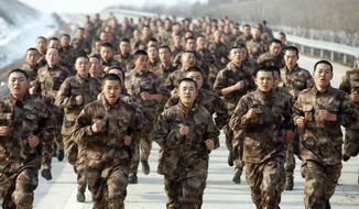 In this Nov. 3, 2015 photo, novice soldiers run along a road during a test of military skills in Heihe in northeastern China's Heilongjiang province. China has created three new military units as part of reforms to modernize its military and improve its fighting capacity. (Chinatopix via AP) CHINA OUT