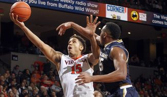 Virginia guard Malcolm Brogdon (15) goes to the basket defended by Notre Dame forward Bonzie Colson (35) during an NCAA college basketball game Saturday, Jan. 2, 2016,  in Charlottesville, Va. Virginia won 77-66. (AP Photo/Andrew Shurtleff)