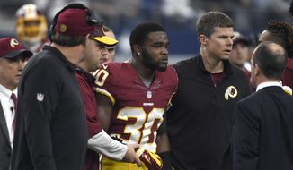 Washington Redskins' Kyshoen Jarrett (30) is assisted off the field by team staff after suffering an unknown injury in the first half of an NFL football game against the Dallas Cowboys on Sunday, Jan. 3, 2016, in Arlington, Texas. (AP Photo/Michael Ainsworth)
