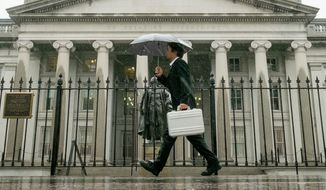 A pedestrian walks past the U.S. Treasury Building in Washington on a rainy day. (Associated Press)