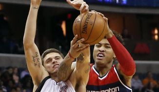 Miami Heat guard Tyler Johnson (8) tries to keep the ball away from Washington Wizards forward Kelly Oubre Jr. (12) in the first half of an NBA basketball game, Sunday, Jan. 3, 2016, in Washington. (AP Photo/Alex Brandon)