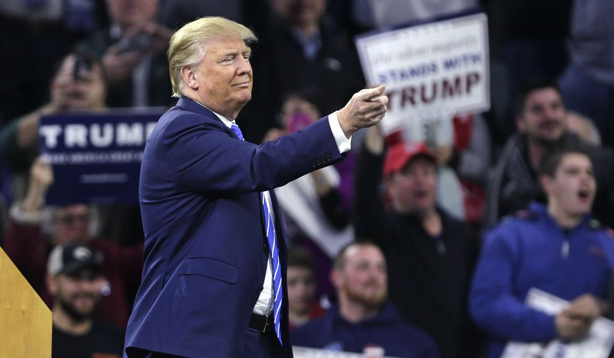 Republican presidential candidate Donald Trump gestures as a protestor is removed from the arena during a campaign stop at the Tsongas Center in Lowell, Mass., Monday, Jan. 4, 2016. (AP Photo/Charles Krupa)