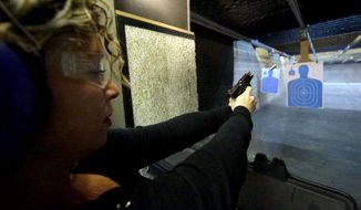Michelle Morrow practices on the shooting range at the Spring Guns and Amo store Monday, Jan. 4, 2016, in Spring, Texas. President Barack Obama defended his plans to tighten the nation's gun-control restrictions on his own, insisting Monday that the steps he'll announce fall within his legal authority and uphold the constitutional right to own a gun. (AP Photo/David J. Phillip)