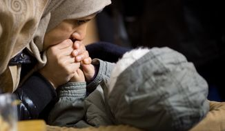 A mother warms the hands of her little child in a tent at the central registration center for refugees and asylum seekers LaGeSo (Landesamt fuer Gesundheit und Soziales - State Office for Health and Social Affairs) LaGeSo during freezing temperatures in Berlin, Germany ,Monday, Jan. 4, 2016. (Kay Nietfeld/dpa via AP)