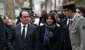 French President Francois Hollande, left, and Paris mayor Anne Hidalgo walk to pay homage to late police officer Ahmed Merabet in Paris, Tuesday Jan. 5, 2016. Hollande is honoring 17 victims killed in Islamic extremist attacks on satirical newspaper Charlie Hebdo, a kosher market and police a year ago this week, unveiling plaques around Paris marking violence that ushered in a tumultuous year. (Benoit Tessier, Pool Photo via AP)