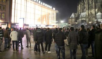 "People are gathered at the Cologne, Germany, main station, in this Dec. 31, 2015, file photo. German police said Wednesday Jan. 6, 2016 that they are investigating whether a string of sexual assaults and thefts at New Year is linked to a known criminal network. The assaults in Cologne last week have prompted outrage in Germany and a fresh debate about immigration, after police said the perpetrators appeared to be of ""Arab or North African origin."" (Markus Boehm/dpa via AP)"