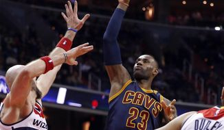 Cleveland Cavaliers forward LeBron James (23) shoots over Washington Wizards center Marcin Gortat, left, during the first half of an NBA basketball game Wednesday, Jan. 6, 2016, in Washington. (AP Photo/Alex Brandon)