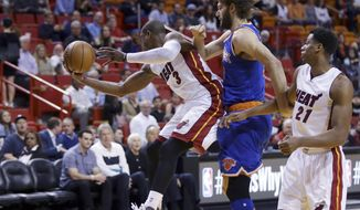 Miami Heat's Dwyane Wade, left, grabs a rebound in front of New York Knicks' Robin Lopez, center, as Miami Heat's Hassan Whiteside (21) looks on during the first half of an NBA basketball game, Wednesday, Jan. 6, 2016, in Miami. (AP Photo/Lynne Sladky)