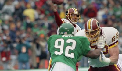 Washington Redskins Mark Rypien passes under pressure from Philadelphia Eagles Reggie White during first quarter action in Wildcard playoff game, Saturday, Jan. 5, 1991 at Philadelphia Veterans Stadium. Holding off White is Redskins Joe Jacoby. Rypien threw two touchdown passes the lead the Redskins to a 20-6 upset win. (AP Photo/Amy Sancetta)