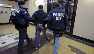 Immigration and Customs Enforcement officers escort an arrestee during a series of early-morning raids on March 3, 2015. (Associated Press)