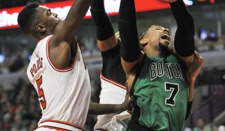Boston Celtics' Jared Sullinger (7), goes up for a shot against Chicago Bulls' Bobby Portis (5), and Taj Gibson (22), during the first half of an NBA basketball game Thursday, Jan. 7, 2016, in Chicago. (AP Photo/Paul Beaty)